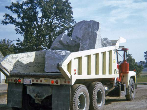 Old dump truck from Hribar Logistics, carrying large stone